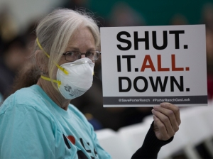 PORTER RANCH, CA - JANUARY 16: A woman holds a sign while attending a public hearing before the South Coast Air Quality Management District (AQMD) regarding a proposed stipulated abatement order to stop a nearby massive natural gas leak, on January 16, 2016 in Granada Hills, near Porter Ranch, California. More than 80,000 metric tons of methane gas have spewed from the Aliso Canyon natural gas storage facility since October 23, causing thousands of Porter Ranch residents to leave their homes, and the closures of two schools where students are being bussed to campuses farther away from the gas. State officials are now concerned that a seventh attempt to plug the well may have increased the chance of a blowout, which would greatly increase the release of gas as well as the risk of a massive well fire if ignited by a spark. The Southern California Gas Company (SoCalGas) hopes to repair the leak by sometime in March. (Photo by David McNew/Getty Images)